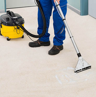 Male Cleaner Vacuuming Floor