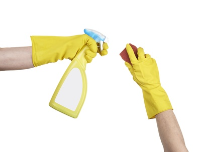 Cleaning surface in bright yellow gloves with sponge and cleanin
